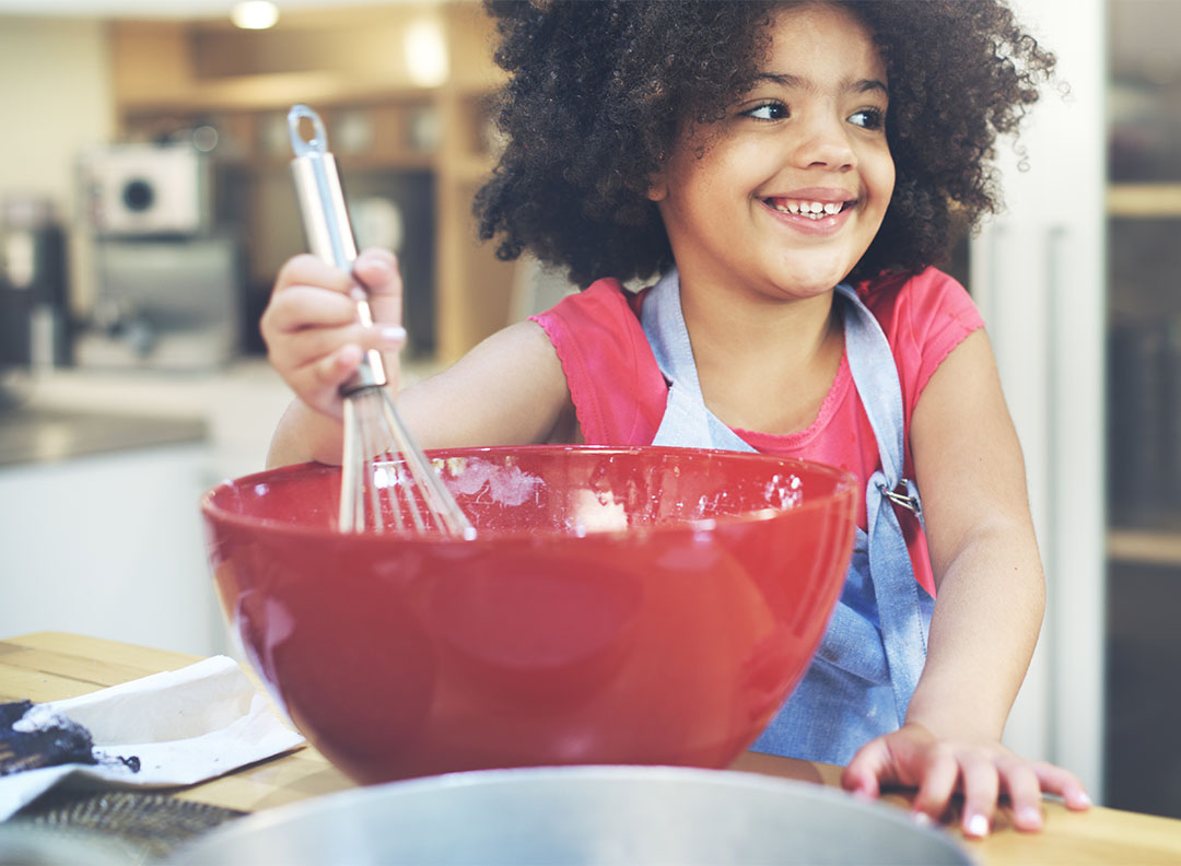 young girl mixing ingredients in a red bowl